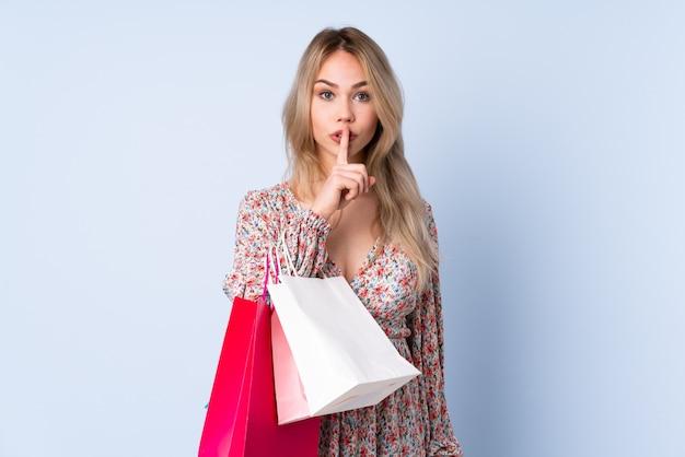 Tiener russisch meisje met het winkelen zak op blauwe muur die een teken van stiltegebaar tonen die vinger in mond zetten