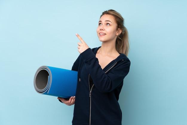 Tiener russisch meisje met mat geïsoleerd op blauw wijzend met de wijsvinger een geweldig idee