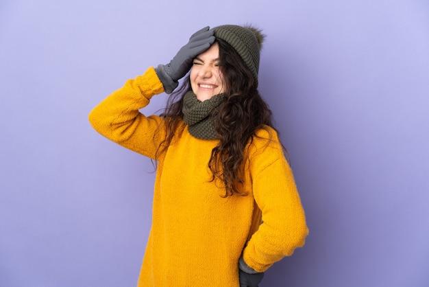 Tiener russisch meisje met wintermuts geïsoleerd op paarse achtergrond lacht veel