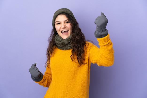Tiener russisch meisje met wintermuts geïsoleerd op paarse achtergrond vieren een overwinning