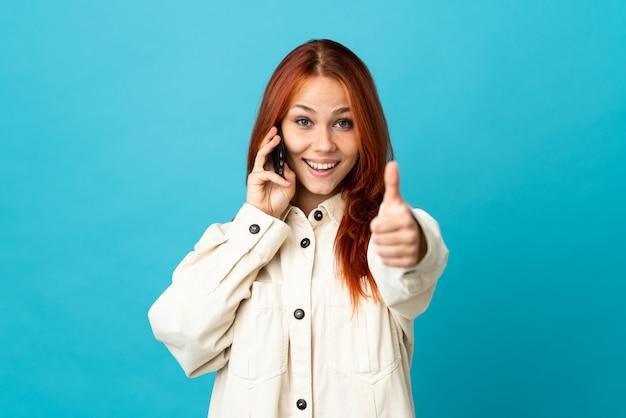 Tiener russisch meisje op blauw met behulp van mobiele telefoon tijdens het doen van duimen omhoog