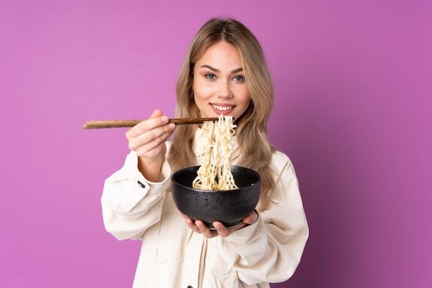 Tiener russisch meisje op purpere muur die een kom noedels met eetstokjes houden en het aanbieden