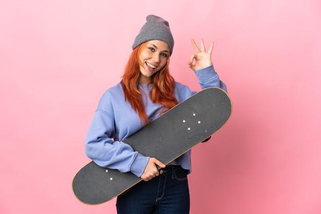 Tiener russisch meisje op roze met een skate en doet ok teken