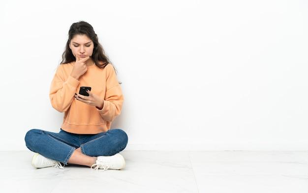 Tiener russisch meisje zittend op de vloer denken en verzenden van een bericht