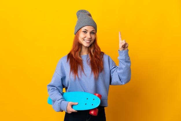 Tiener russisch schaatsermeisje op geel die en een vinger in teken van het beste tonen opheft