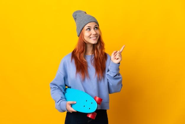 Tiener russisch skatermeisje op geel die een geweldig idee benadrukt