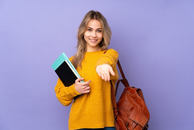 Tiener russisch studentenmeisje dat op purpere muur copyspace denkbeeldig op de palm wordt geïsoleerd om een advertentie in te voegen