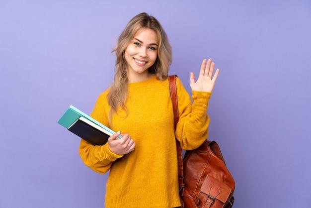 Tiener russisch studentenmeisje dat op purpere muur wordt geïsoleerd die met hand met gelukkige uitdrukking groet