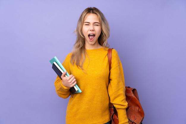 Tiener russisch studentenmeisje dat op purpere muur wordt geïsoleerd die naar voren schreeuwt met wijd open mond