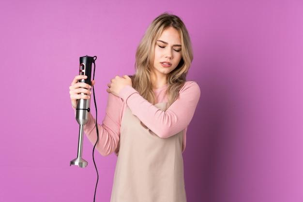 Tiener russische vrouw die handmixer gebruikt die op purpere muur wordt geïsoleerd die aan pijn in schouder lijdt voor het hebben van een inspanning