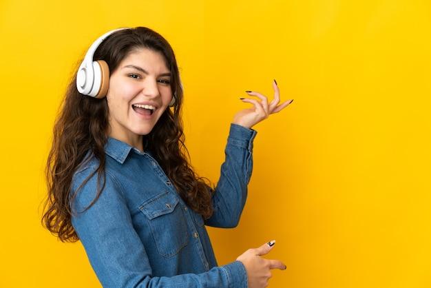 Tiener russische vrouw die op gele muur wordt geïsoleerd die aan muziek luistert en gitaargebaar doet