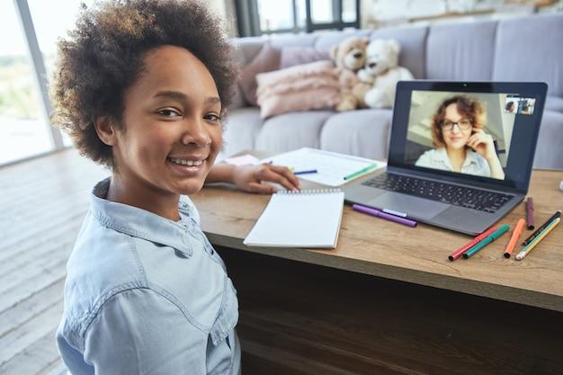 Tiener schoolmeisje lacht naar de camera terwijl ze online les heeft met haar leraar via de videochat-app