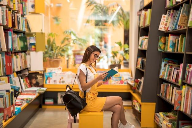 Tiener schoolmeisje met boek op stoel