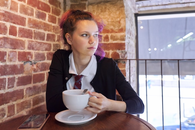 Tiener schoolmeisje zit in een café met een kopje cappuccino
