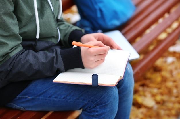 Tiener schrijven in notitieblok zittend op een bankje in herfst park, close-up