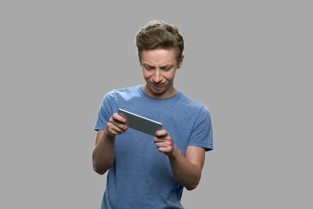 Tiener speelspel op mobiele telefoon. aantrekkelijke tienerjongen ondergedompeld in gamen. oplossing voor verslaving aan mobiele telefoons voor tieners.