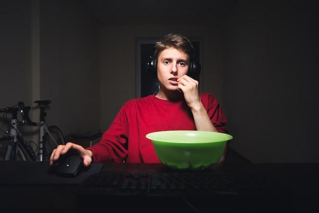 Tiener speelt 's nachts videogames op de computer en eet chips