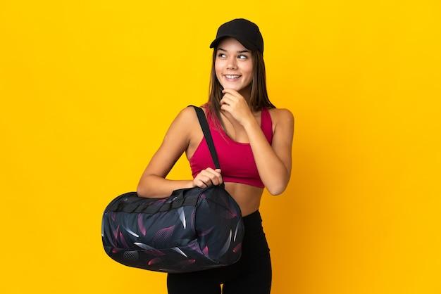 Tiener sport meisje met sporttas op zoek naar de kant en glimlachen