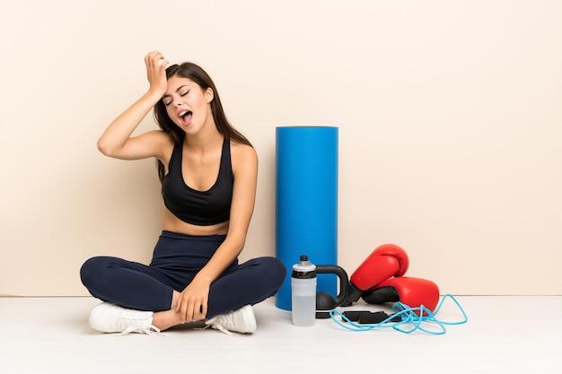Tiener sport meisje zittend op de vloer heeft iets gerealiseerd en de oplossing voornemens