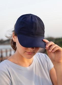Tiener staande bij de zee bij zonsondergang. tienermeisje dat een t-shirt en een donkerblauwe baseballpet draagt en het vizier aanraakt. mockup voor pet en t-shirt