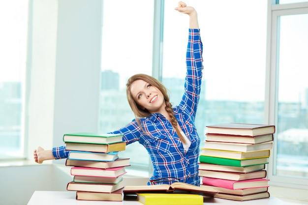 Tiener stretching haar armen terwijl het bestuderen
