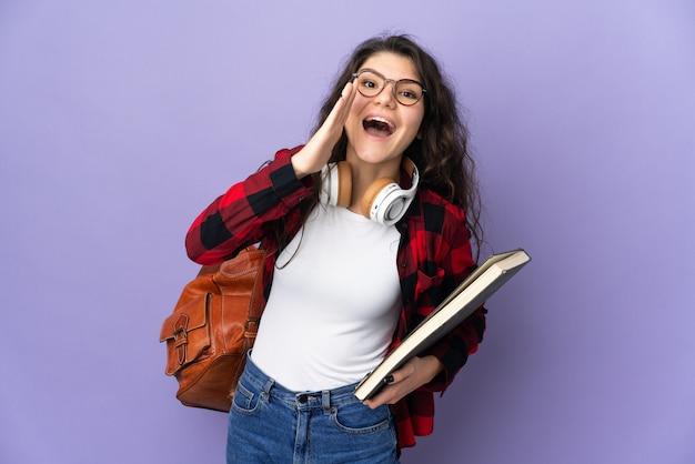 Tiener student geïsoleerd op paarse achtergrond schreeuwen met mond wijd open