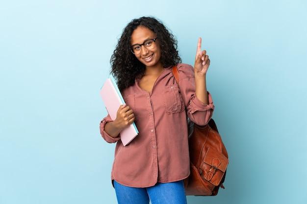 Tiener student meisje geïsoleerd op blauwe achtergrond die een geweldig idee benadrukt