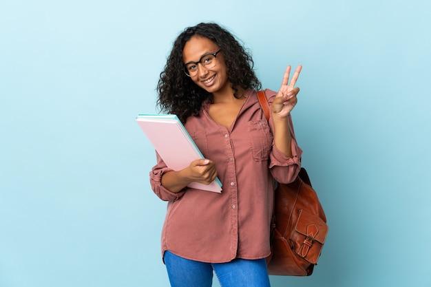 Tiener student meisje geïsoleerd op blauwe achtergrond glimlachend en overwinning teken tonen