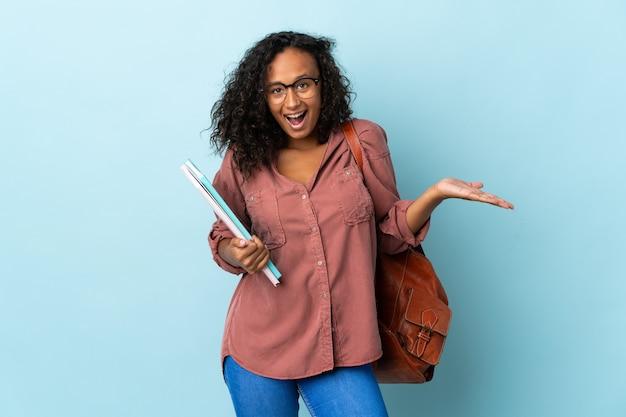 Tiener student meisje geïsoleerd op blauwe achtergrond met geschokte gelaatsuitdrukking