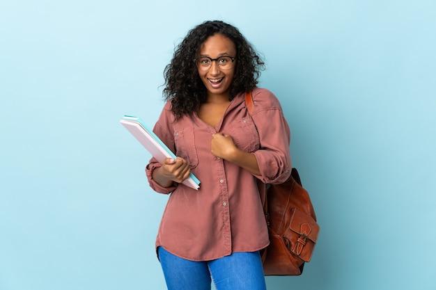 Tiener student meisje geïsoleerd op blauwe achtergrond met verrassingsgelaatsuitdrukking