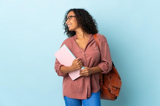 Tiener student meisje geïsoleerd op blauwe achtergrond op zoek kant
