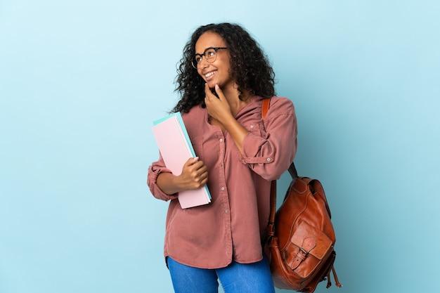 Tiener student meisje geïsoleerd op blauwe achtergrond op zoek naar de kant en glimlachen