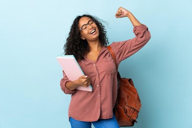 Tiener student meisje geïsoleerd op blauwe achtergrond sterk gebaar doen