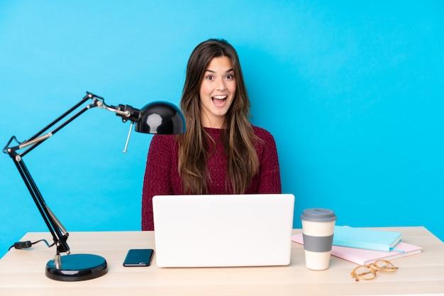 Tiener student meisje op een werkplek over blauwe muur
