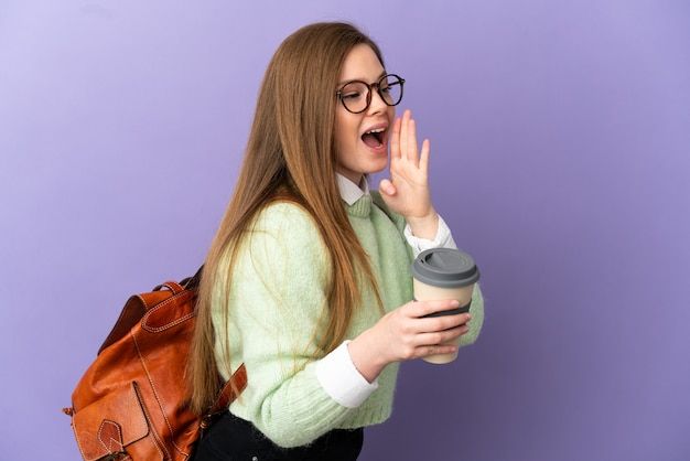 Tiener student meisje over geïsoleerde paarse achtergrond schreeuwen met mond wijd open naar de zijkant