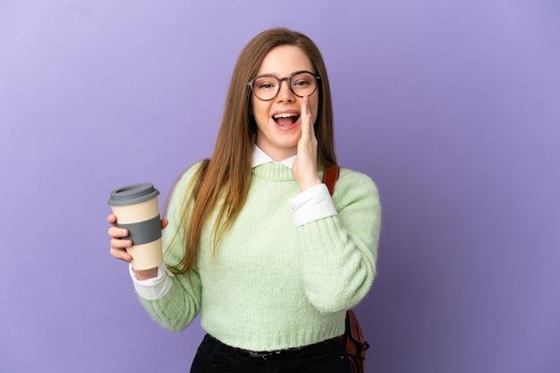 Tiener student meisje over geïsoleerde paarse achtergrond schreeuwen met mond wijd open