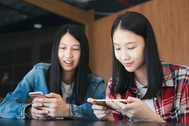 Tiener student met behulp van digitale mobiele telefoon