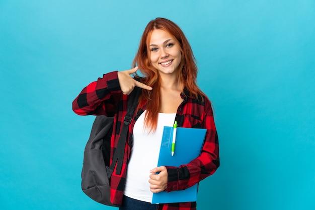 Tiener student russisch meisje geïsoleerd op blauwe achtergrond trots en zelfvoldaan
