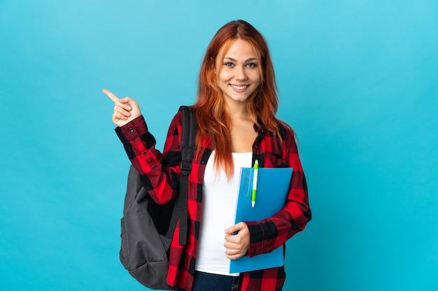 Tiener student russisch meisje op blauwe wijzende vinger naar de zijkant