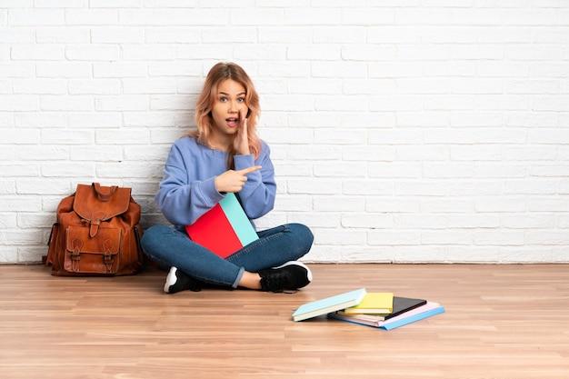 Tiener student vrouw met roze haar zittend op de vloer binnenshuis wijzend naar de kant om een product te presenteren en iets te fluisteren