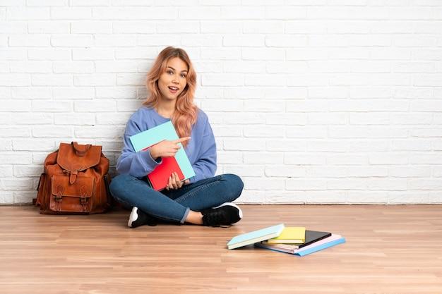 Tiener student vrouw met roze haren zittend op de vloer binnenshuis terug te wijzen