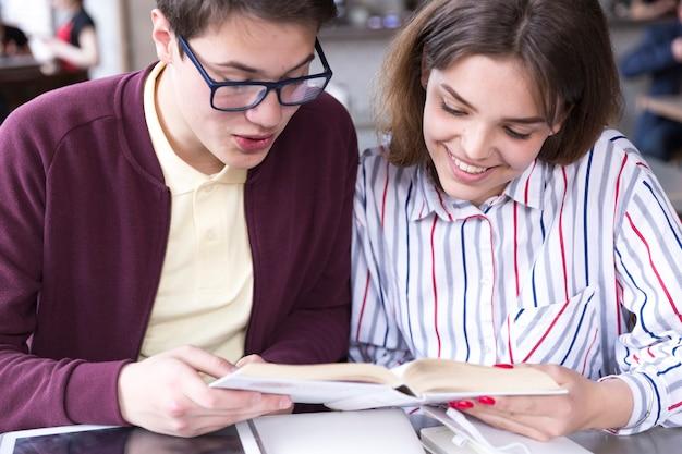 Tiener studenten zitten aan tafel en het lezen van boek