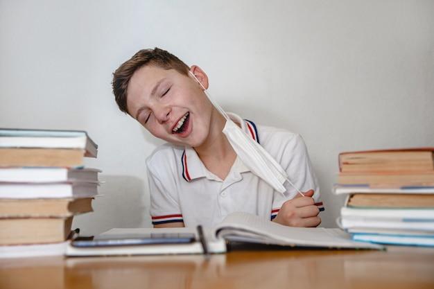 Tiener thuis voor schoolboeken trekt met een opgeluchte glimlach zijn masker af