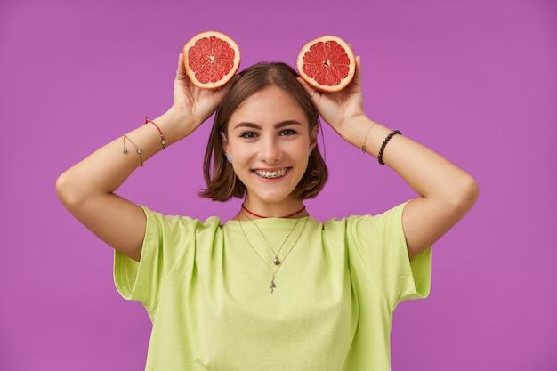 Tiener, vrolijke en gelukkige glimlachende dame met kort donkerbruin haar die grapefruit boven haar hoofd houden. staande over paarse muur. het dragen van een groen t-shirt, tandenbeugels, armbanden en ketting