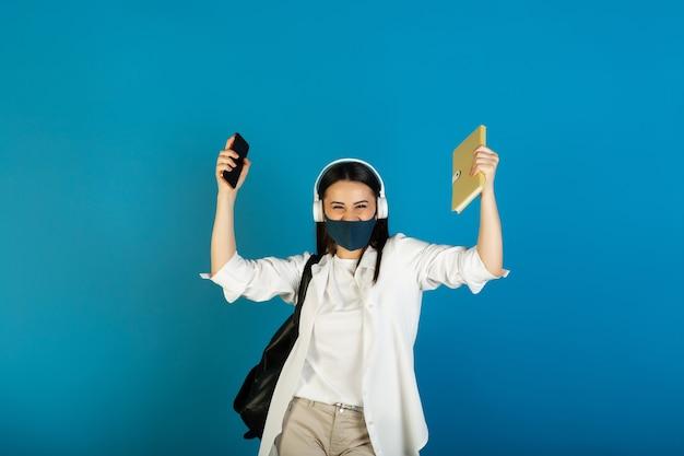 Tiener vrouw die met rugzak gezichtsmasker en hoofdtelefoons draagt die gele blocnote en telefoon op blauw houden