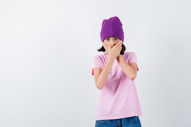 Tiener vrouw hand in hand op mond in t-shirt en muts ziet er bang uit