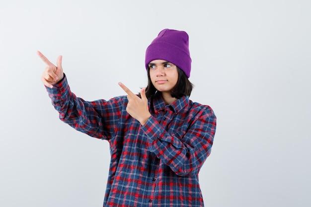 Tiener vrouw in geruit hemd en muts gebaren geïsoleerd
