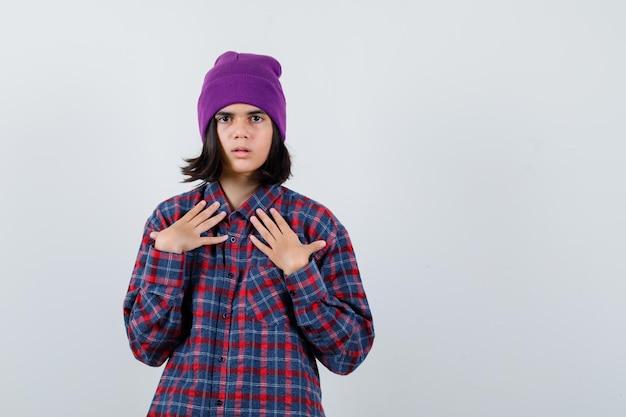 Tiener vrouw in geruit hemd en muts hand in hand op de borst en kijkt gefocust