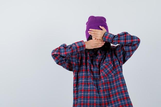 Tiener vrouw in geruit hemd en muts hand in hand op gezicht en ziet er onwel uit