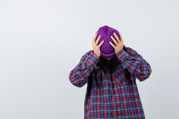 Tiener vrouw in geruit hemd en muts omklemd hoofd met handen op zoek gestrest